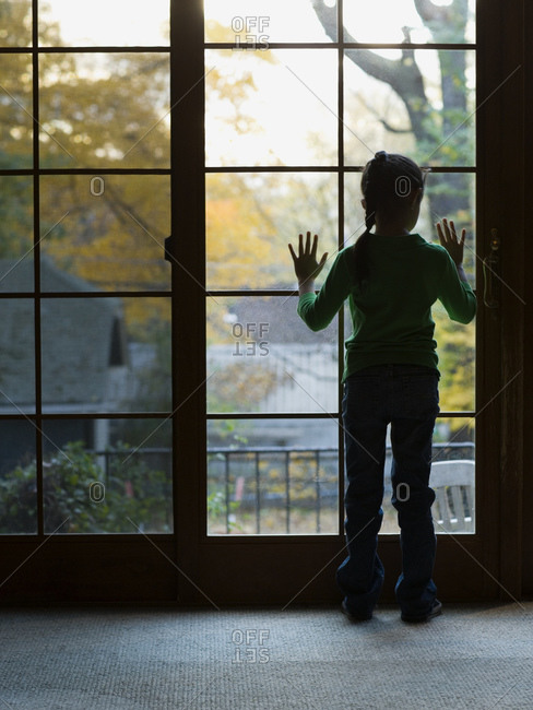 Young girl looking through large window