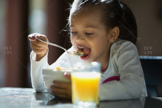 Young girl eating cereal and glass of orange juice