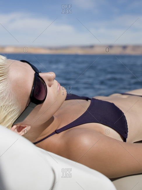 Woman in bikini sunbathing on boat