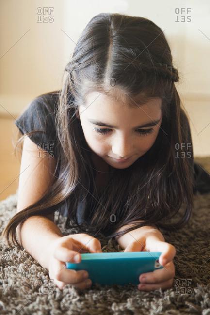 Girl (8-9) playing mobile phone game