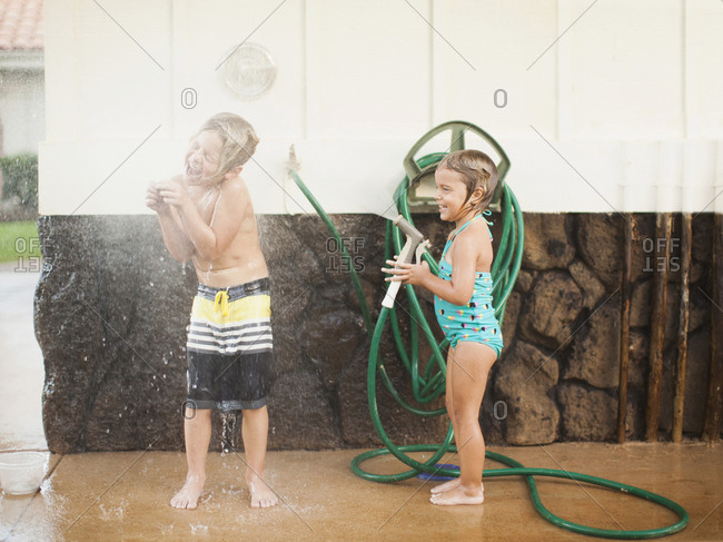 Children (2-3, 6-7) refreshing with garden hose