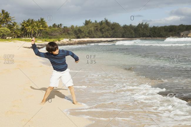 Boy (10-11) playing on beach