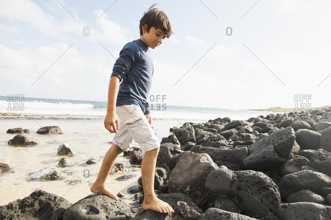 Boy (10-11) walking on stones on beach