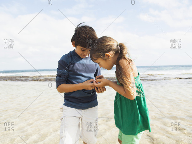 Portrait of girl (6-7) and boy (10-11) on beach