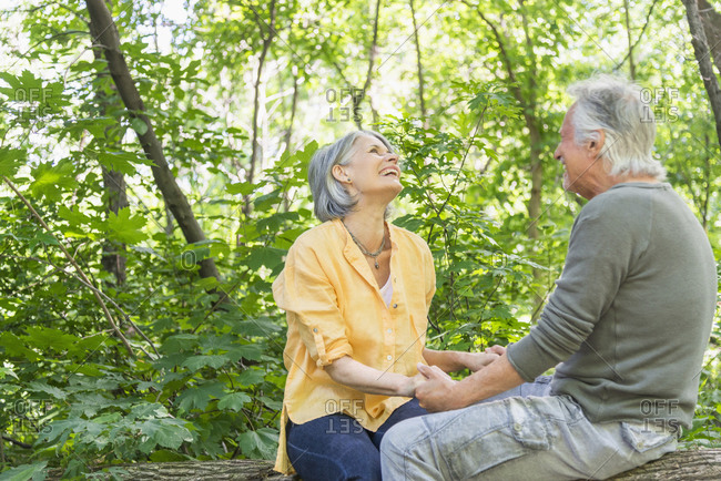 Senior couple sitting on log in forest