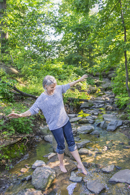 Senior woman crossing stream