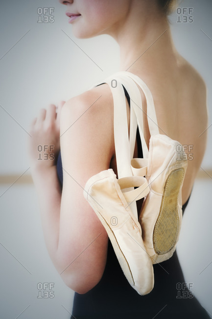 Mid section of teenage (16-17) ballet dancer holding ballet shoes