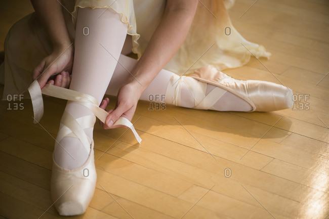Close up of ballet dancer (16-17) tying her ballet shoe