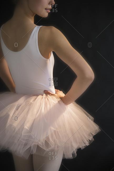 Teenage (16-17) ballerina with hand on hip wearing tutu