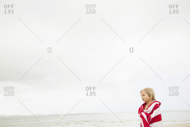 Boy (6-7) wrapped in towel on beach