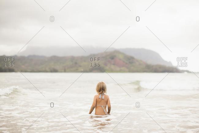 Baby girl (2-3) wading in ocean