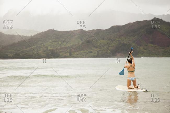 Woman paddling on shallow water