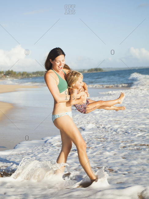Mother with daughter (2-3) playing on beach