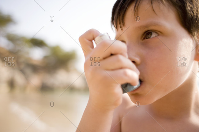 Asthmatic boy using his inhaler