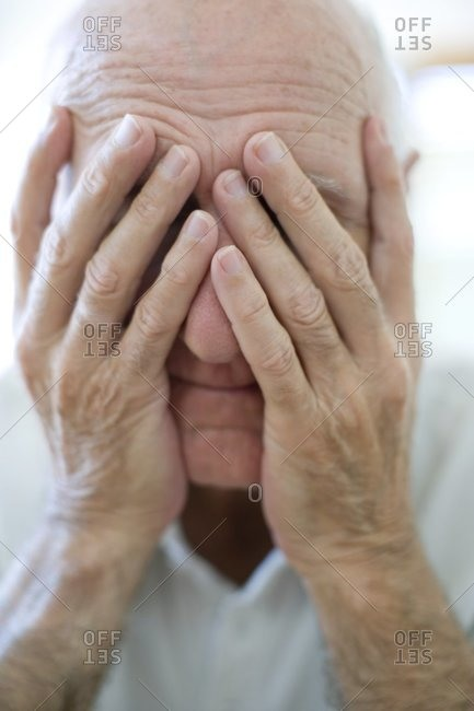 Depressed man covering his face with his hands