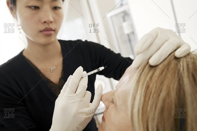 Clinician examining a female patient's forehead, following a botox injection