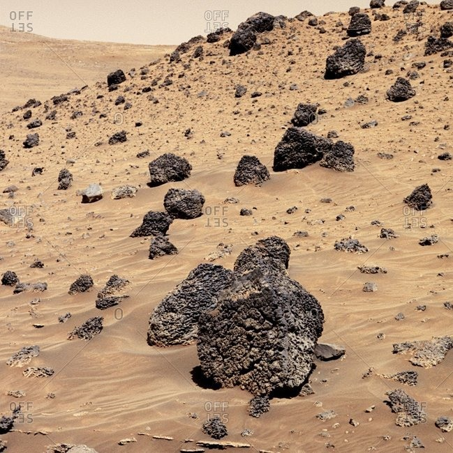 True-color image of Martian rocks on the slope of the 'Low Ridge' feature of the Gusev Crater. The dark, pockmarked rocks (one seen in the foreground) are thought to be volcanic in origin. This image was obtained by the Mars Exploration Rover Spirit.