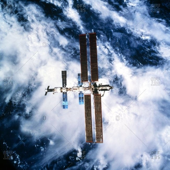 International Space Station (ISS) orbiting above the Earth. Blue and brown solar panels extend out from the ISS, providing power for the Station.