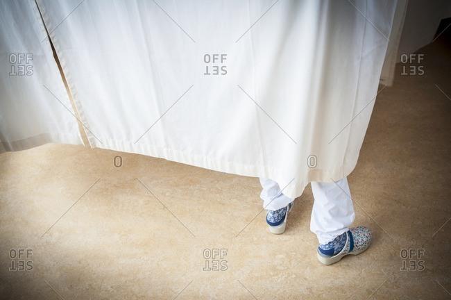 Hospital ward, nurses feet behind a curtain