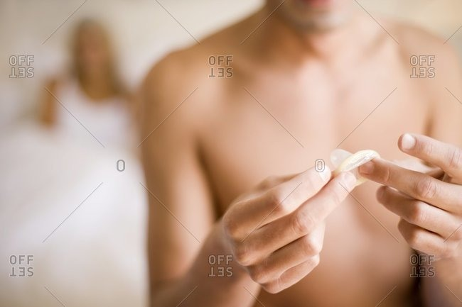 Man unwrapping a condom. His girlfriend is sitting in bed behind him.