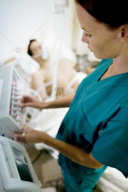 Nurse adjusting controls on a ventilator attached to an unconscious patient