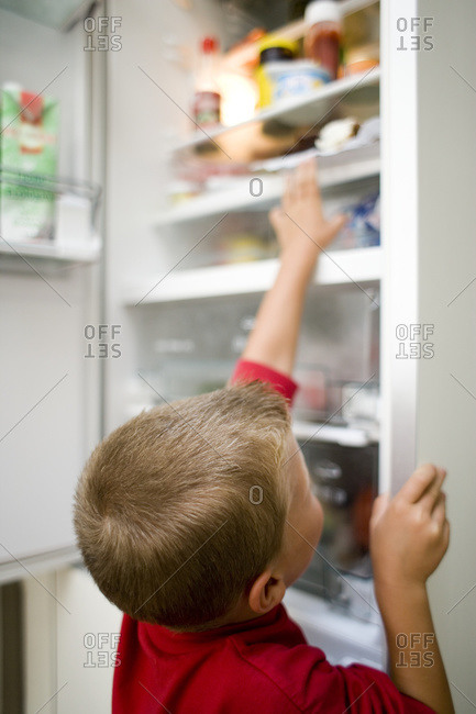 Boy looking in fridge and grabbing an item of food.