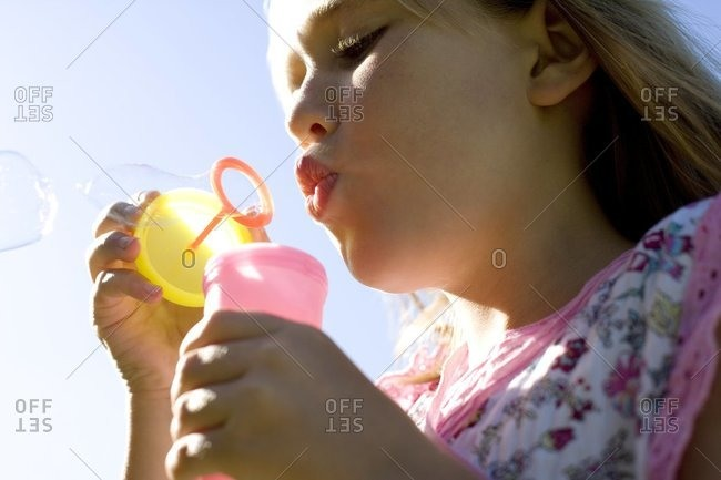Girl blowing soap bubbles through a wand
