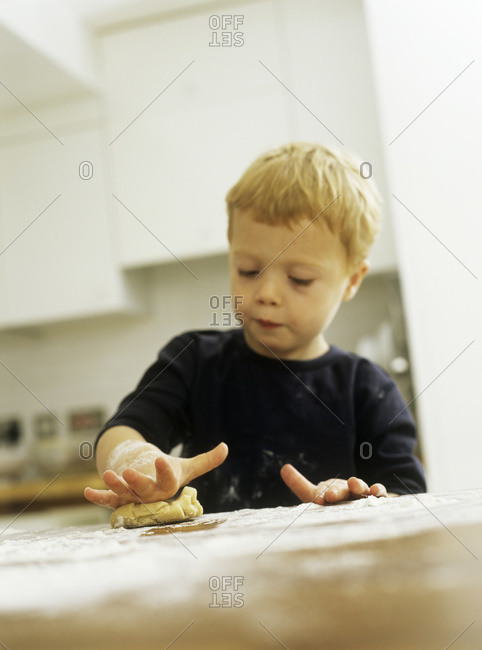 Three year old boy rolling a biscuit dough.