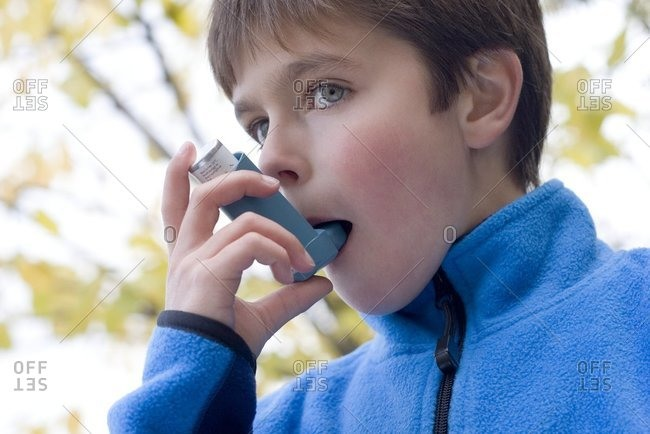 Treating an asthma attack. Boy using an inhaler to treat an asthma attack.