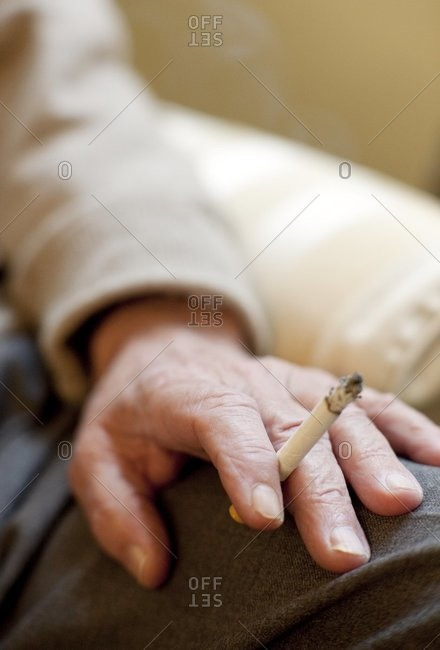 Smoking. Senior man holding a cigarette.