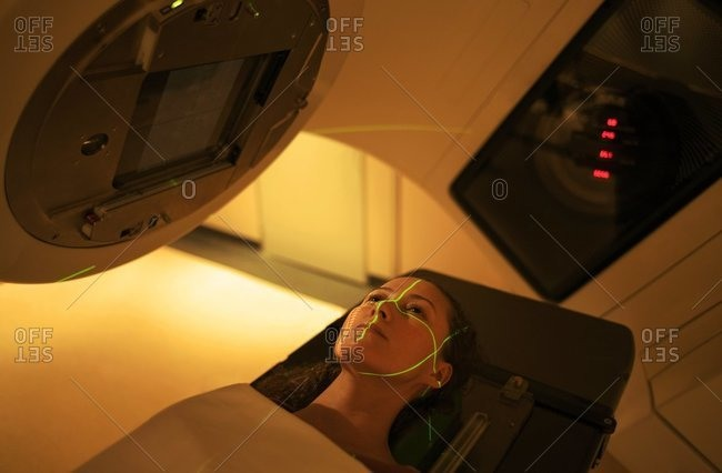 Woman undergoing radiation treatment, radiotherapy.