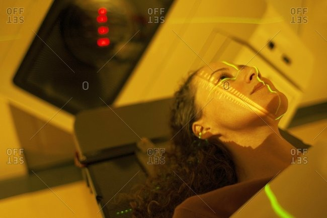 Lasers being aligned on a woman's face prior to radiation treatment, radiotherapy.