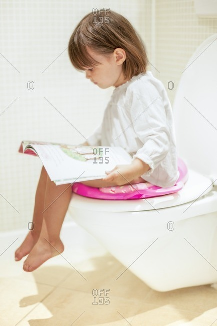 Toddler reading on the toilet.