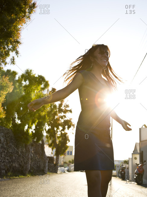 Woman standing on street in silhouette with arms up backlit