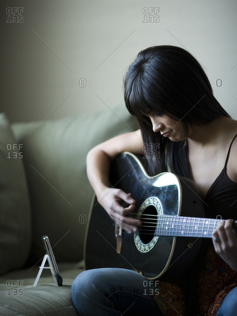 Woman tuning guitar with metronome
