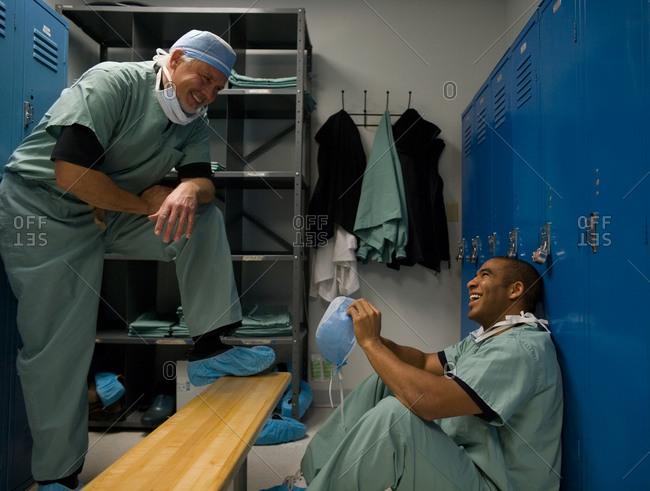 Male doctors in scrubs talking in locker room
