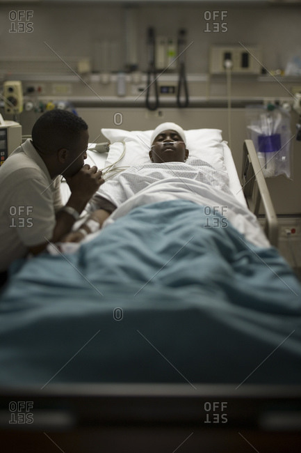 Boy in hospital bed with head bandages with father by his side