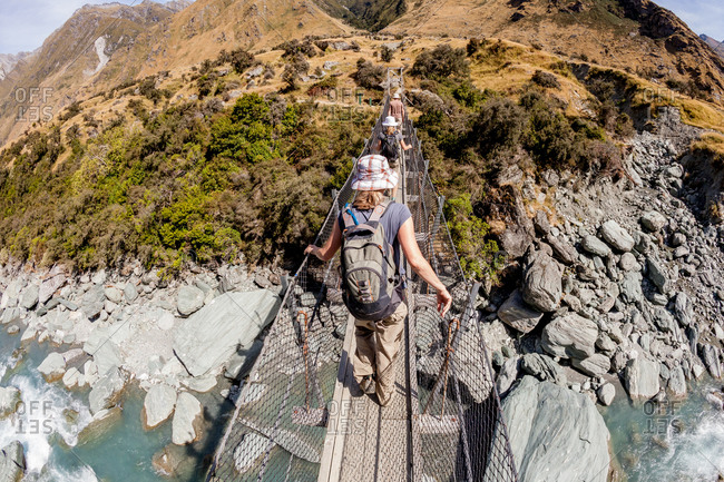 Rear view of people crossing suspended bridge in mountains