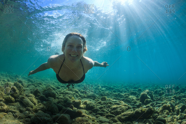 Portrait of young woman swimming underwater