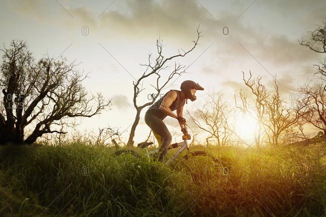 Asian man riding dirt bike in tall grass