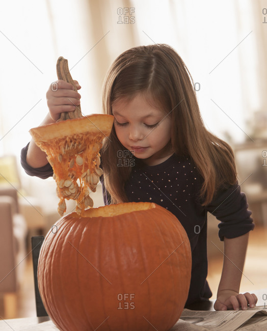 Caucasian girl carving pumpkin at table