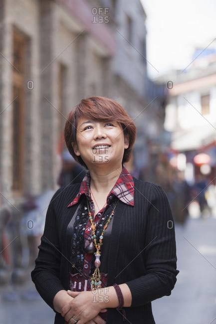 Older Chinese woman walking on city street
