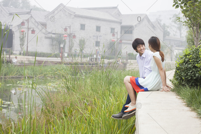 Chinese couple talking by creek