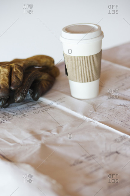 Coffee cup and gloves on blueprints