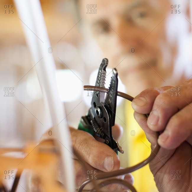 Close up of Caucasian man snipping wire