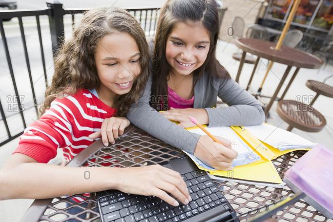 Smiling girls using laptop at cafe