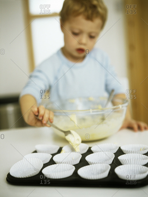 Three year old boy placing cake mixture into individual paper cases before they are baked in an oven.