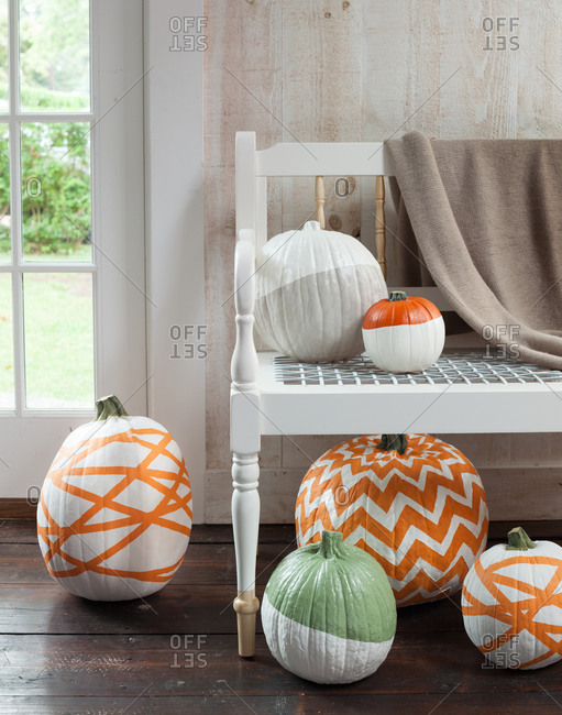 Different painted pumpkins around bench