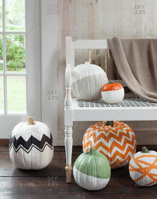 Different painted pumpkins around bench