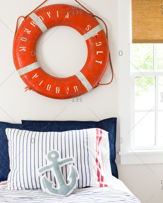 Nautical bedroom interior with life preserver on the wall
